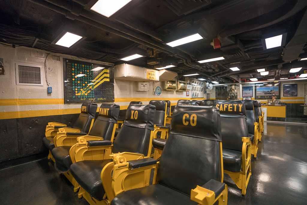 Yellow and black seats in the pilot ready room in the San Diego USS Midway Museum